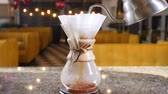 maker : Modern and alternative ways of coffee making.Barista brews coffee using Coffee maker. Close up of hands pouring hot water into paper filter with Coffee. Slow motion