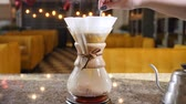 brewed : Modern ways of coffee making. Close up of a barista making hand brewed coffee. Stirring ground coffee in paper filter with a spoon.Slow motion Stock Footage