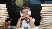 mente : Modern school concept. Attractive girl sits at a desk with heaps of books. and a blackboard behind her. positive schoolgirl in headphones smiles. thumbs up. Stock Footage