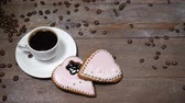 cup and saucer : Food art. Good morning concept. cup of coffee and 2 heart-shaped gingersnaps are on wooden background. Coffee beans fall down in slow motion