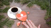 podšálek : Food art.Broken heart. Fir tree, a cup of fresh-brewed coffee and heart-shaped gingersnaps placed on wooden background.one cookie is broken into pieces Top view.Female hands takes a piece.