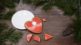 cup and saucer : Food art. Broken heart. Fir tree, a cup of fresh-brewed coffee and heart-shaped gingersnaps placed on wooden background.one cookie is broken into pieces Top view. Female hands takes out a cup Stock Footage