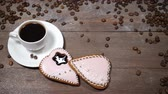 sörfőzés : Food art. Good morning concept. cup of coffee and 2 heart-shaped gingersnaps are on wooden background. Coffee beans fall down in slow motion