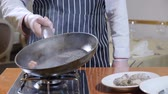 kaynama : Eating out. Food preparation. Close up of chef holding a pan with boiling oil and a garlic. slow motion. oil splashes Stok Video