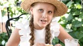 rogalik : Portrait of cute little girl with a straw hat on eating out in a street cafe. She eats a cheese croissant and smiles