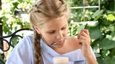 rágás : Portrait of pleasant-looking girl drinking hot chocolate licking sweet foam off a straw in city park. Lifestyle. Child enjoys sun Stock mozgókép