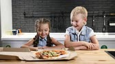 urvat : Kids eating. Two pretty kids opening pizzabox and watching pizza in delight. Favourite food for children. 4k
