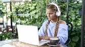 Young pretty girl sitting in a street restaurant with a white laptop on table. Lifestyle concept. Schoolgirl listening to music in Coffee house with a terrace. 4k
