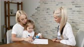 Child Health Examination. Young mother and her little pretty daughter visit pediatrician. Friendly child health clinic. Mom and doc talking 4k Stock Footage