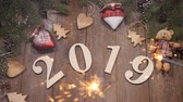 above fire : Happy New Year 2019 concept. Top view on 2019 figures on wooden background decorated with pine branches and handmade toys. Bengal fire all around. Slow motion