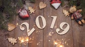 pohlednice : New year 2019 concept. Christmas theme. Wooden numerical symbols 2019 placed on wooden background. Bengal fire all around. hd