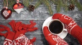 cartões : Merry Christmas and happy new year 2019 2020 concept. Hands in red knitted mittens take a cup of hot coffee off a wooden background where new year symbols are placed. Fir tree branches, christmas toys and red knitted scarf.