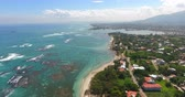 Flying over beautiful ocean waves to exotic coastline with houses and palms. 4k. Top view