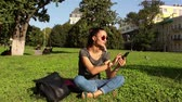 jovial : Beautiful young girl sits on the grass in the park and listens to her favorite tune on the phone, shaking her head to the beat of the music. Stock Footage