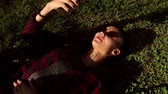 jovial : Beautiful young girl in sunglasses and plaid shirt, lying on grass and listening to music on her phone.