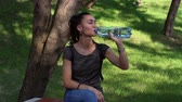 girlish : Young beautiful girl smiles and enjoys drinking water from a plastic bottle. Stock Footage