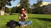 Beautiful young girl wearing sunglasses, sitting on the grass in the park, turning on her favorite melody in the phone.