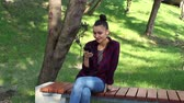 Young beautiful girl in a plaid shirt is sitting on a park bench, smiling and writing a message in her smartphone.