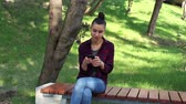 Young beautiful girl in a plaid shirt sits on a bench in the park, actively rewritten in internet chat. Filmati Stock