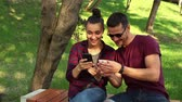 zdjecia : Couple in love show photos on their smartphones with each other, sitting on a park bench. Wideo