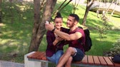momentka : Young lovers take a selfie ,sitting on a park bench.