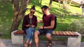 Young loving couple, on a sunny day, is actively discussing a new smartphone while sitting on a bench in the park.