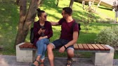 Young couple in love is photographed sitting on a bench in the park.They are smiling and hugging each other. Stockvideo
