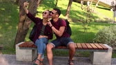 Young couple in love is photographed sitting on a bench in the park.They are smiling and hugging each other. Wideo