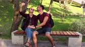 momentka : Young couple in love is photographed sitting on a bench in the park.They are smiling and hugging each other. Dostupné videozáznamy