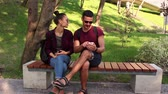 momentka : Couple in love show photos on their smartphones , sitting on a park bench. Dostupné videozáznamy