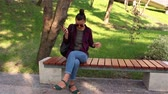 Young beautiful girl listening to music in her smartphone, sings and dances while sitting on a park bench.