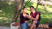 Couple in love show photos on their smartphones , sitting on a park bench. Filmati Stock