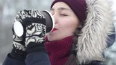 vacuuming : Beautiful young girl enjoy winter view and drinks coffee in the snowy park.