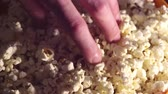A man takes fresh hot popcorn from a bowl. A male hand picks popcorn from a bucket.