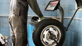 yenilemek : Kherson, Ukraine 20 October 2016: Tire service Mechanic balancing a car wheel on automated machine checking readout on the digital display before adding the weights in Kherson, 20 October 2016.