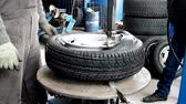 yenilemek : Kherson, Ukraine 20 October 2016: Tire service Man put on tyre on car wheel by special tool, mechanic using tire mounting tool machine in Kherson, 20 October 2016. Man Mount Tire On Wheel Rim Stok Video