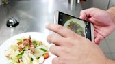ingredient : Caesar salad on mobile phone screen, chef photographs food on professional kitchen in restaurant, Photo Food mobile phone, ready meal in the cafe before serving visitors