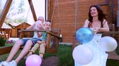 chain : holiday for dad mom and baby, portrait of a happy family on a summer vacation, Family riding a seesaw, parents hold in hand colored balloons, fun, laughing,