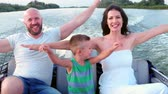 embarcaram : happy family riding on a boat, parents with a child having fun summer day, quickly go along the river by speedboat, happy mother, father and son, hands outstretched enjoying vacation