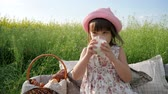delighted : Lovely girl on flower meadow with basket for Picnic, female child in panama with bun on nature, Weekend at picnic, Girl on flower meadow with pastries and milk, Happy joyful child Stock Footage