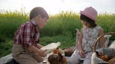 fogyasztás : kids at picnic, Boy and girl with food on nature, Happy children in fresh air, Boy pours milk into glass for girl, Bread and dairy products eating, during rest, Holiday in nature,