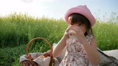 близнецы : healthy kid drinks milk from glass, sweet girl beverage from dairy products, Pleasure on childs face, milk advertising, Healthy food for children, little female child at picnic drinks, Стоковые видеозаписи