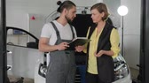 sektör : portrait sad client in service station, woman and master near machine, visitor in auto repair, service book in hand auto mechanic, mechanician helps customer, guy pro advises client,