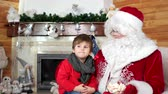 marshmellow : little kid telling santa his christmas wishes, room with fireplace, boy visiting santa claus winter residence, sweets for good and obedient children, holiday atmosphere, child sit on saint nicolas lap Stock Footage