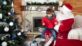 congratulação : santa welcomes little boy, kid getting christmas present sitting on santa claus lap, presents for good and obedient children, holiday atmosphere, child visiting saint nicolas winter residence, x-mas