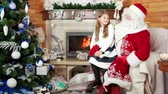 cláusula : girl sitting at santa lap, happy kid telling papa noel his christmas wishes, smiling young lady, room with fireplace and decorated christmas tree, santa claus winter residence, holiday atmosphere