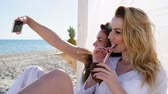 tentador : Selfphoto friends on beach, girls photographed on android Shoot selfies, coconut in hands of young woman, beautiful girlfriends in swimsuits take pictures phone near ocean, white curtains on bungalow Stock Footage