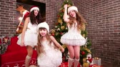 papai noel : Three sisters in carnival costumes dancing near Christmas tree, Happy family celebrating New Years Eve, Christmas fun three girlfriends, New Year party in Santas house, Santa hat