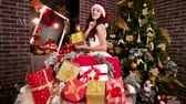 jak : Sexy girl Santas helper gives gifts to New Year to children, Sending an air kiss girl gives Christmas surprise, In New Years room lot of bright surprises for children, Sexy elf and New Years gifts,