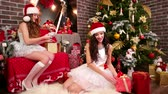 obter : Girls prepare New Years cards and gifts to friends, Two friends pack festive boxes near Christmas tree, Funny winter holidays, Santa helpers arrange presents for children, Beautiful carnival costume